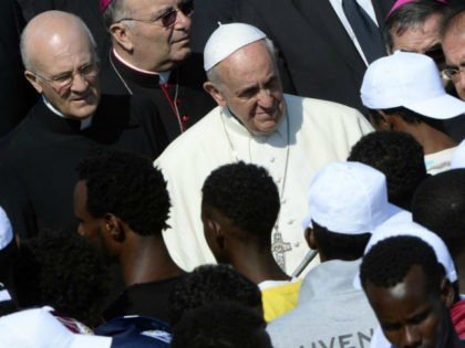 Pope Francis (C) speaks to migrants during his visit to the island of Lampedusa, a key destination of tens of thousands of would-be immigrants from Africa, on July 8, 2013. Pope Francis called for an end to 'indifference' to the plight of refugees on Monday on a visit to an …