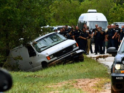 Police investigators watch as the van containing the six members of the the Saldivar family who died is towed to the road after they crashed their van into Greens Bayou as they tried to flee Hurricane Harvey during heavy flooding in Houston, Texas on August 30, 2017. / AFP PHOTO …