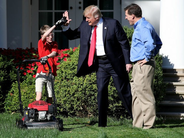 WASHINGTON, DC - SEPTEMBER 15: 11-year-old Frank 'FX' Giaccio (L) high fives U.S. President Donald Trump (C) while mowing the grass in the Rose Garden of the White House September 15, 2017 in Washington, DC. Giaccio, from Falls Church, Virginia, who runs a business called FX Mowing, wrote a letter …