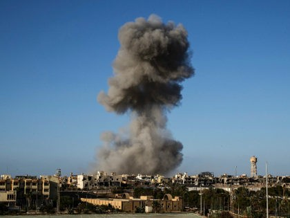 TOPSHOT - Smoke rise after an airstrike on the District 3 of Sirte, the last stronghold of Islamic State (IS) on September 28, 2016. France will host an international meeting on strife-ridden Libya next week featuring several countries in the region including Egypt and Gulf states, the French government's spokesman …