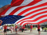 Participants carry an American flag during the 4th of July parade in Santa Monica, Calif. on Tuesday, July 4, 2017. Decked out in red, white and blue, Californians waved flags and sang patriotic songs at Independence Day parades across the state. Americans (AP Photo/Richard Vogel)
