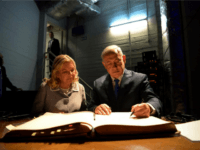 In this picture released by the Israeli Government Press Office, Israeli Prime Minister Benjamin Netanyahu, right, and his wife Sara sign the visitors book at the AMIA Jewish community center in Buenos Aires, Argentina, Monday, Sept. 11, 2017. The bombing of the Argentine-Israeli Mutual Association in downtown Buenos Aires killed …