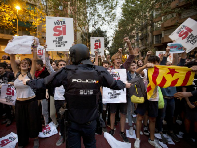 In this photo taken on Wednesday, Sept. 20, 2017, a Spanish national police officer tries to stop demonstrators protesting outside the main offices of the left wing party CUP in Barcelona, Spain. A confrontation between the central government in Madrid and independence movements in the wealthy northeastern Catalonia region has …