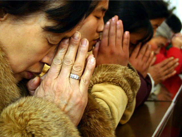 Chinese Christians pray during a midnight mass on Christmas eve at a church in Beijing, China, Friday, Dec. 24, 2004. Chinese authorities insist that Christians worship only in government-controlled churches. Despite harassment, fines and the possibility of prison, millions of Protestants and Catholics continue to attend unauthorized assemblies, including in …