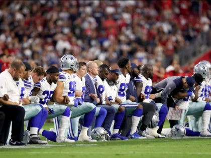 dallas-cowboys-link-arms-take-a-knee-during-national-anthem-getty