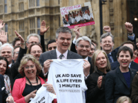 MPs and campaigners from Non Governmental Organisations take part in a photocall following the passing of a law of a committing Britain to spend 0.7% of its gross national income on foreign aid on March 9, 2015 in London, England.