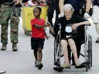 In this Sept. 3, 2005 file photo, Tanisha Belvin, 5, holds the hand of fellow Hurricane Katrina victim Nita LaGarde, 89, as they are evacuated from the Convention Center in New Orleans, La. Hundreds of people waited several days to be evacuated. (AP Photo/Eric Gay, File)
