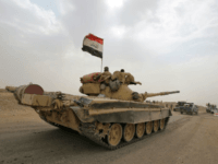 Iraqi soldiers pictured on a Russian-made T-72 tank as they advance towards the city of al-Sharqat, north of Baghdad, on September 20, 2017