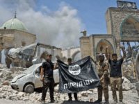 Iraqi troops hold a captured Islamic State group flag beside the ruins of the Al-Nuri Mosque on June 30, 2017 as victory over the jihadists in Mosul neared