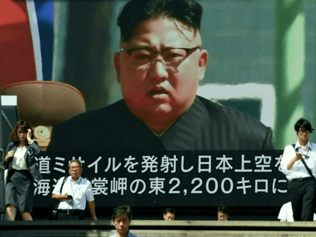 Pedestrians walk in front of a large TV screen in Tokyo broadcasting a news report on North Koreas latest missile test