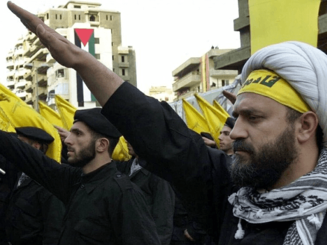 Hezbollah fighters take an oath during a parade to continue the path of resistance towards Israel.