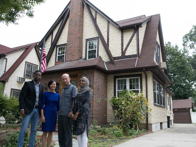 In this Saturday, Sept. 16, 2017 photo, Abdi Iftin, left, of Somalia, Uyen Nguyen, second from left, of Vietnam, Eiman Ali, right, of Somalia born in Yemen, and Ghassan al-Chahada, of Syria pose for a photo outside President Donald Trump's boyhood home in the Jamaica Estates neighborhood of the Queens borough of New York. The house that Trump's father built is now a rental available on Airbnb. The international anti-poverty organization Oxfam rented it Saturday and invited refugees to share their stories with journalists. (AP Photo/Mary Altaffer)