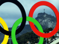 The Christ the Redeemer statue is seen through a set of Olympic rings in Rio de Janeiro