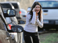 FILE - In this Dec. 14, 2012 file photo, Carlee Soto uses a phone to get information about her sister, Victoria Soto, a teacher at the Sandy Hook Elementary School in Newtown, Conn., after gunman Adam Lanza killed 26 people inside the school, including 20 children. Victoria Soto, 27, was among those killed. On Wednesday, Dec. 14, 2016, Newtown is planning to mark the fourth anniversary of the Sandy Hook Elementary School shooting with a moment of silence. (AP Photo/Jessica Hill, File)