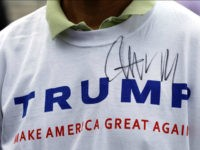 FILE - In this Aug. 29, 2015, file photo, Donald Trump supporter John Wang wears a shirt autographed by the Republican presidential candidate outside the National Federation of Republican Assemblies in Nashville, Tenn. It's been a tumultuous political summer. The unexpected rises of billionaire Donald Trump and socialist Bernie Sanders. …
