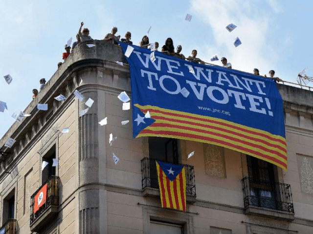 A group of people in Barcelona throw ballots for the October 1 referendum from a building with a banner in favour of the referendum, with Spain's prime minister asking Catalan leaders to admit their plans have been dealt a serious blow.