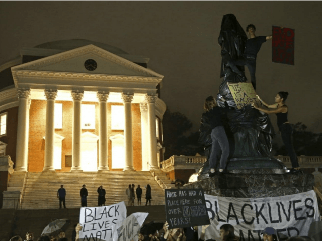 "Protesters cover a statue of Thomas Jefferson with black tarp in front of the rotunda at the University of Virginia on Sept. 12, the one-month anniversary of the ""Unite the Right"" rally in Charlottesville. (Zack Wajsgras/Daily Progress/AP)"