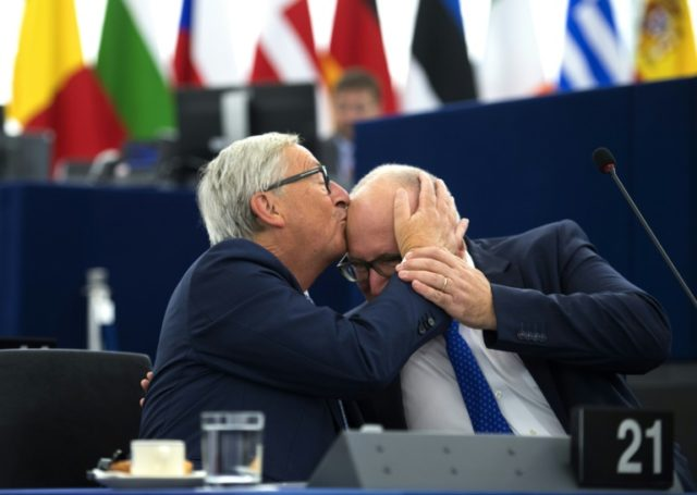 Bald is beautiful: European Commission chief Jean-Claude Juncker (L) kisses his deputy, Frans Timmermans, before delivering his State of the Union speech