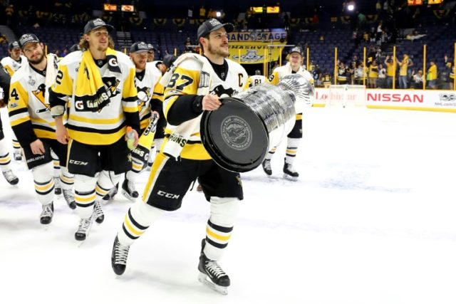 Sidney Crosby and his Pittsburgh Penguins teammates celebrate with the trophy after defeating the Nashville Predators 2-0 to win the 2017 NHL Stanley Cup Final, at the Bridgestone Arena in Nashville, Tennessee, on June 11, 2017