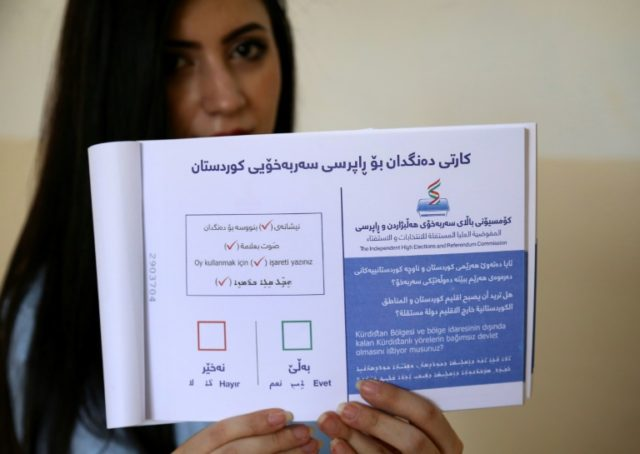 Yes or no: an employee with the Kurdish electoral commission in Arbil shows a ballot book for Monday's vote