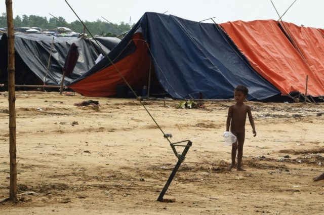 A young Rohingya refugee stands amongst makeshift shelters in the refugee camp of Kutupalong near the locality of Ukhia on September 21, 2017