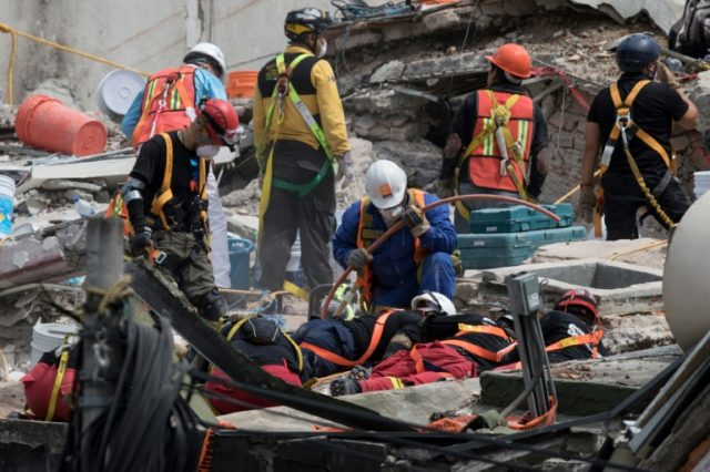 Rescuers work on the cleanup of a collapsed building in search of survivors in Mexico City