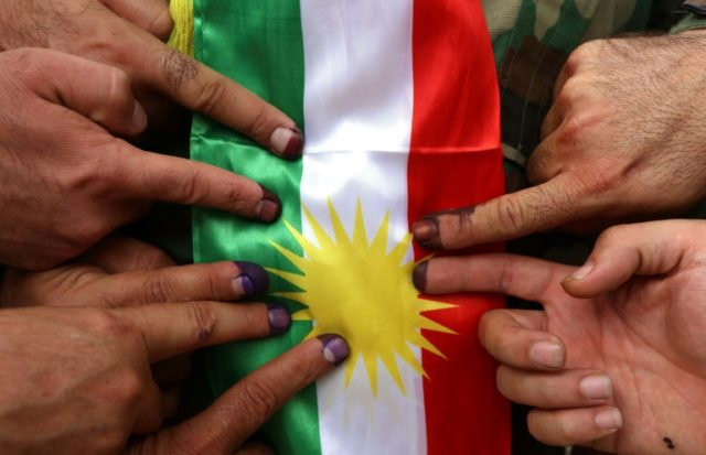 Kurdish Peshmergas place their ink-stained fingers on a Kurdish flag after voting in the Kurdish independence referendum in Arbil, the capital of the autonomous Kurdish region of northern Iraq, on September 25, 2017
