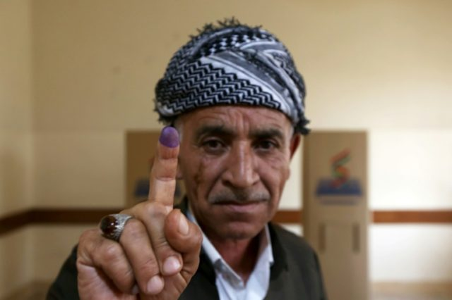 An Iraqi Kurd shows off his ink-stained finger after voting on Iraqi Kurdistan's independence in regional capital Arbil
