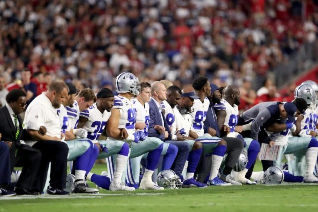 Members of the Dallas Cowboys link arms and kneel during the National Anthem before the start of their NFL game against the Arizona Cardinals, at the University of Phoenix Stadium in Glendale, Arizona, on September 25, 2017
