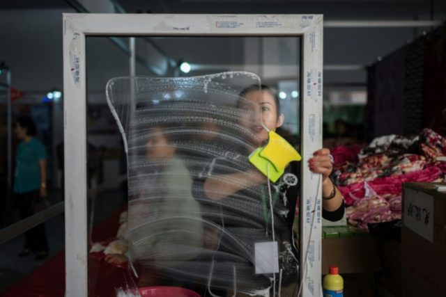 A vendor displays a window cleaning product at the Pyongyang trade fair