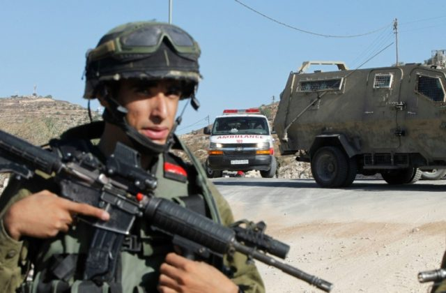 A member of Israeli security force stands guard near a checkpoint in the West Bank