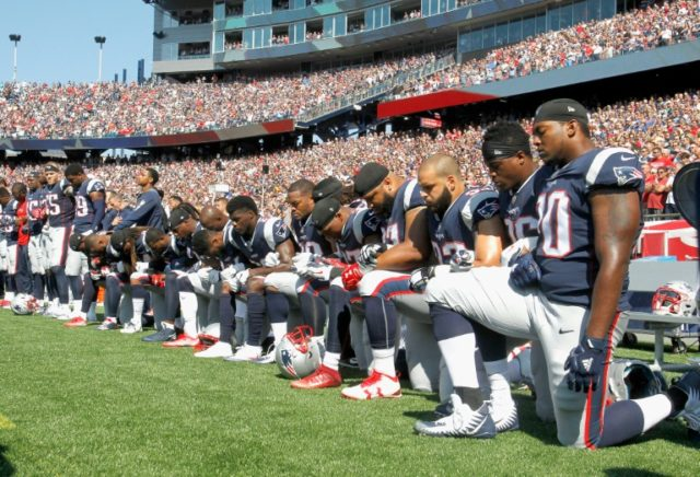 Members of the New England Patriots kneel during the National Anthem before their game against the Houston Texans, at Gillette Stadium in Foxboro, Massachusetts, on September 24, 2017