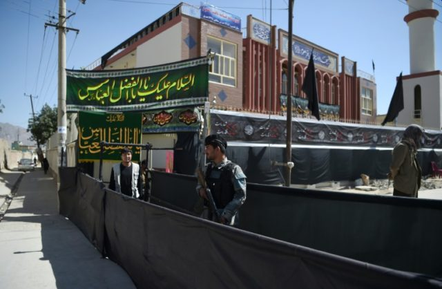 An Afghan policeman stands guard outside of the Baqir ul-Uloom mosque ahead of Ashura in Kabul