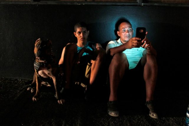 A man checks his cell phone next to a road at night in one of a few places with cell signal in San Juan, Puerto Rico