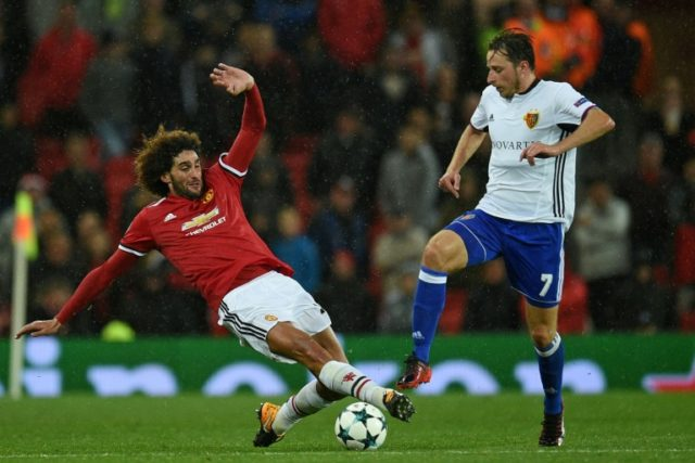 Manchester United midfielder Marouane Fellaini (L) tackles Basel midfielder Luca Zuffi during the Champions League Group A match at Old trafford in Manchester on September 12, 2017