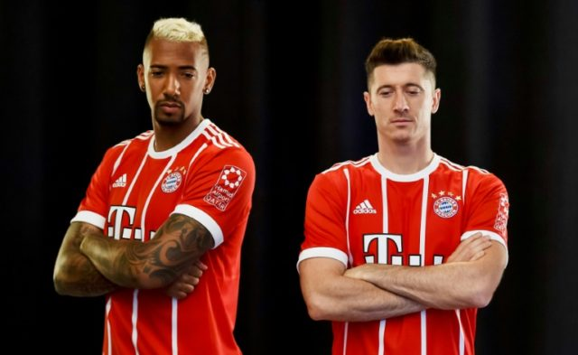 The logo for Qatar's Hamad International Airport is seen on the left sleeve of the jersey of Bayern Munich's defender Jerome Boateng (L), seen with striker Robert Lewandowski in September 2017, where it will stay until 2023