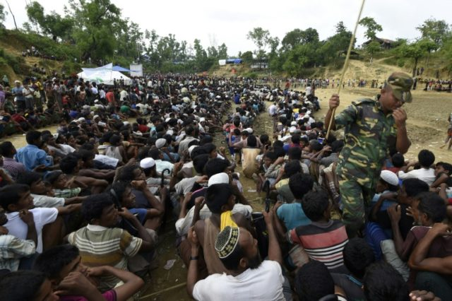 Rohingya Muslim refugees wait as food is distributed by the Bangladeshi army at Balukhali refugee camp near Gumdhum on September 26, 2017