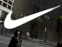 Nike reported a drop in first-quarter earnings on flat sales as heavy promotions in North America again cut into profit