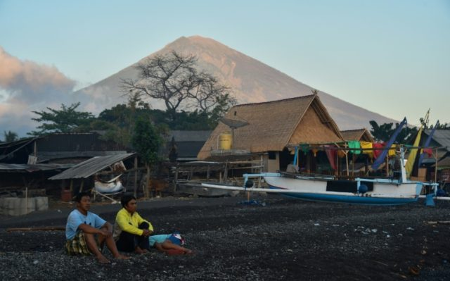 Locals sit near huts and fishing boats on Amed beach, one of the tourist resorts nearest to the Mount Agung volcano, on the island of Bali