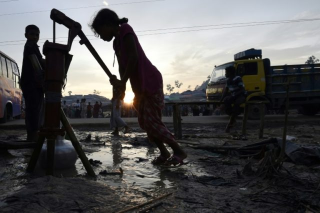 A young Rohingya refugee pumps water at a refugee camp in Bangladesh