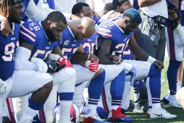 Buffalo Bills players kneel during the national anthem before their NFL game against the Denver Broncos on Sunday