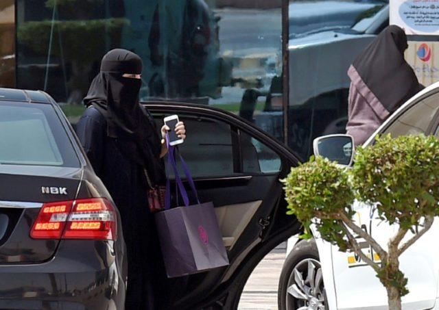 A Saudi woman disembarks from a car outside a mall in the capital Riyadh, a day after Saudi Arabia said it will allow women to drive from next June