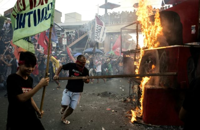 Activists burn an effigy during a protest against Philippine President Rodrigo Duterte to denounce drug war killings and what they say is a slide towards tyranny