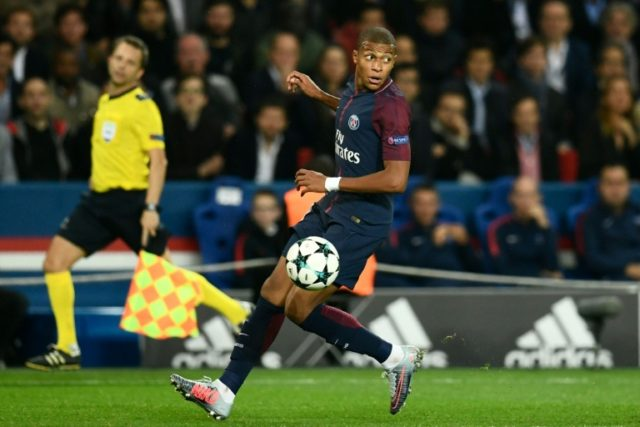 Paris Saint-Germain's French forward Kylian Mbappe lines up with the ball during the match against Bayern Munich at the Parc des Princes stadium