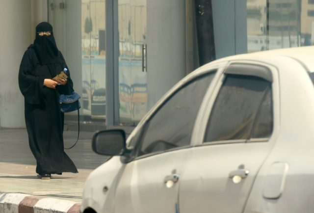 A woman walks down a street in Riyadh on September 27, 2017, after Saudi Arabia decided to allow women to drive from next June