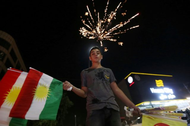 An Iraqi Kurdish man waves the Kurdish flag in the northern city of Arbil as he celebrates the 'yes' vote in an independence referendum, on September 27, 2017