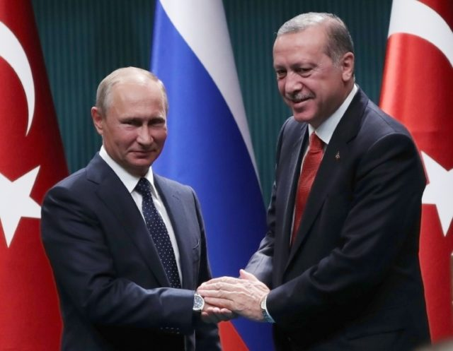 Turkish President Recep Tayyip Erdogan (R) and Russian President Vladimir Putin (L) shake hands after a joint press conference following their meeting at the Presidential Complex in Ankara on September 28, 2017