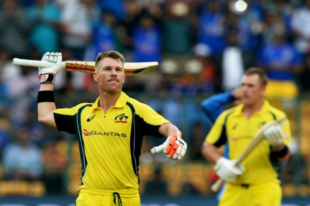 Australian cricketer David Warner (L) celebrates his century (100 runs) during the fourth one day international against India