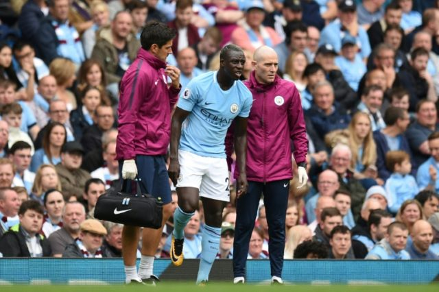 Manchester City's defender Benjamin Mendy (C) is helped by medics on September 23, 2017
