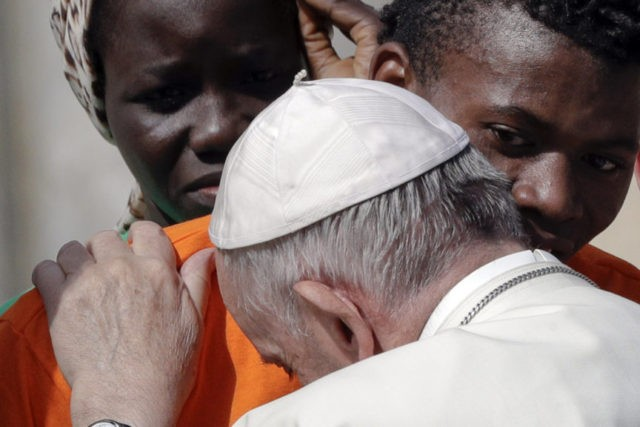 Pope Francis embraces a migrant, during his weekly general audience, at the Vatican, Wednesday, Sept. 27, 2017. Pope Francis on Wednesday launched a two-year activism and awareness-raising campaign about the plight of migrants to counteract mounting anti-immigrant sentiment in the U.S., Europe and beyond. (AP Photo/Andrew Medichini)